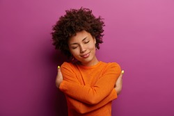 Lovely pretty woman embraces herself, feels good, comfortable and fullfilled, has high self esteem, tilts head and closes eyes, being egoisitc person, wears orange jumper isolated on purple background