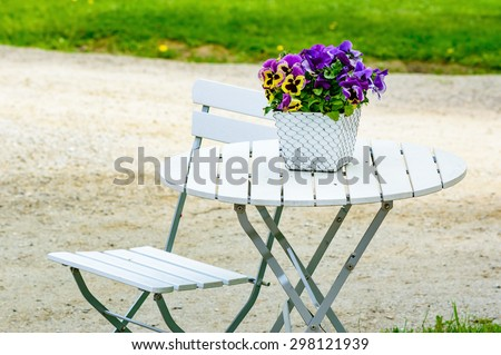 Lovely purple and yellow pansy flowers on white outdoor furniture. Furniture has metal details and wooden surface. One chair and table. Flowerpot has netting on outside. Gravel and grass in background