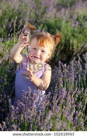 Lovely red hair little girl with beads in a lavender field