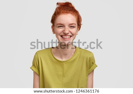 Lovely red haired girl with positive expression, laughs as watches funny TV show, enjoys weekend, dressed in green t shirt, has freckled skin, isolated over white background, amused by comic idea #1246361176