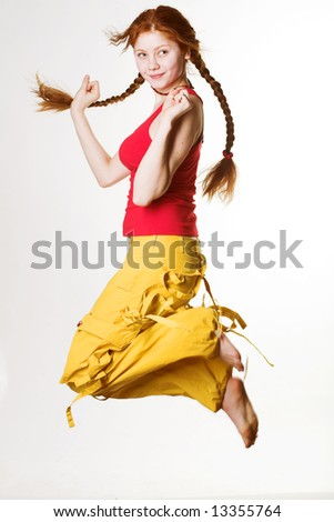 lovely redhead girl with long braids jumps on white background