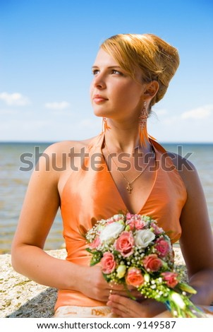 Lovely redhead lady with a bouquet of flowers near the sea