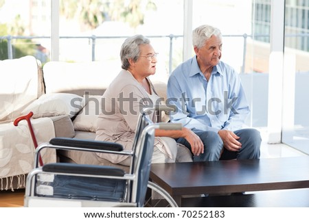 Lovely retired couple talking on the sofa - stock photo