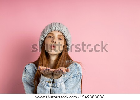 Lovely romantic redhead caucasian girl with clean skin blowing air kiss from open palms to camera , expressing love and affection isolated over pink studio background. Body language, tender feelings.