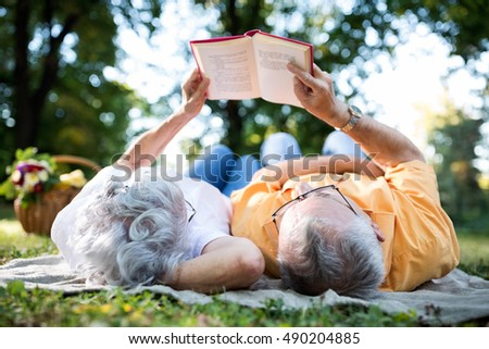 Lovely senior couple resting at park, reading a book