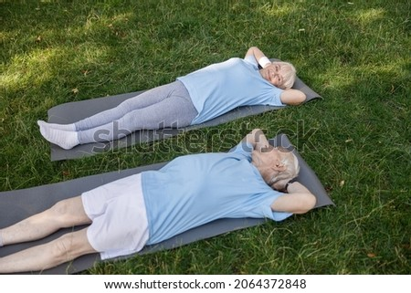 Lovely senior family couple looks at each other lying on mats after training in green park