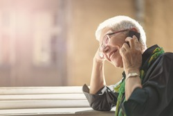 Lovely senior lady having a fun conversation with her friend or a relative