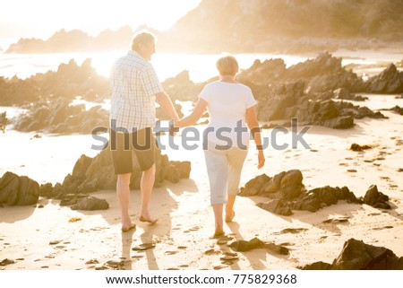 lovely senior mature couple on their 60s or 70s retired walking happy and relaxed on beach sea shore in romantic aging together and retirement husband and wife lifestyle concept #775829368