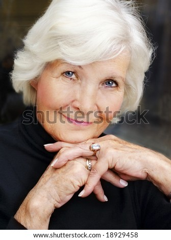 Lovely senior woman portrait on dark background, looking graciously
