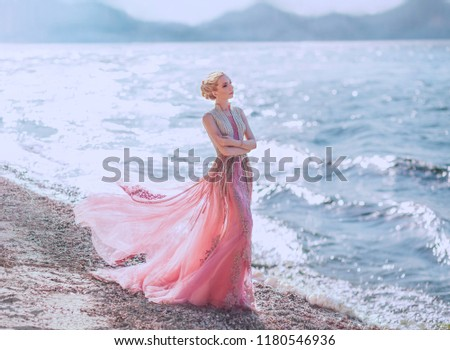 Stock Photo lovely slender girl in a light pink dress is walking along the sandy shore of the beautiful blue sea. glare of the sun is reflected in the waves. wonderful elegant princess elf with blond wavy hair