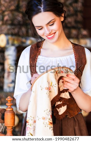 Lovely Smiling Caucasian Brunette Woman Posing With Fancywork Hoop in Retro Dress In Rural Environment. Vertical Image Stock photo ©