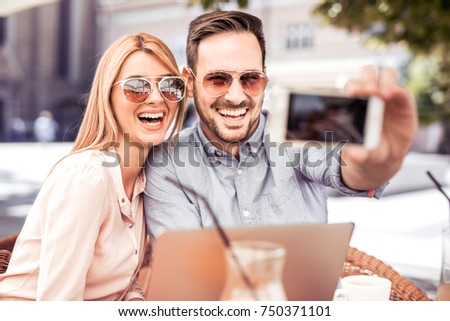 Lovely smiling couple taking selfie with smart phone while sitting in cafe. #750371101