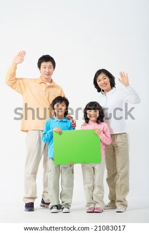 Lovely Smiling Family with green board - raising hands in greeting
