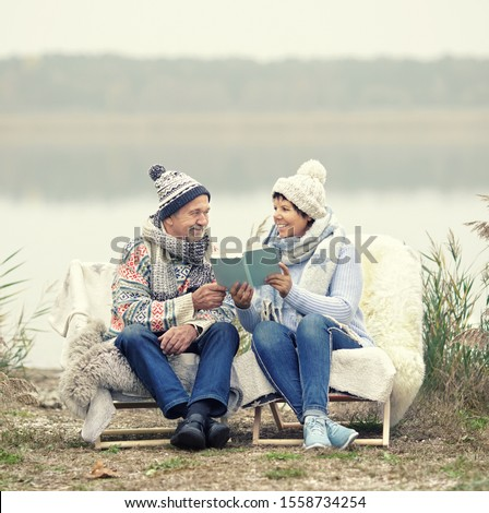 lovely smiling senior couple sitting on the winter beach in warm blanket chair and reading a book stock photo