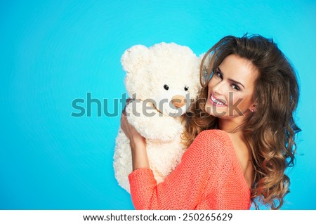 Lovely smiling young woman in knitted clothes holding big soft teddy bear on isolated blue background