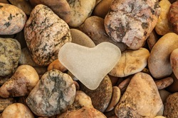 Lovely smoothed and frosted sea glass heart on colorful sea pebbles background. Clouse-up texture of Baltic Sea stones and sea glass.
