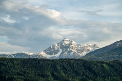 Lovely snowcapped mountains with a sea of green european alps