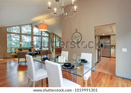 Photo of Lovely spacious open floor plan with vaulted ceiling and tan walls features dining area with glass top table and living room with window wall.