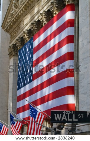 Lovely sun-dappled view of the historic New York Stock Exchange building draped in an American flag, with Wall Street street sign, full field focus.
