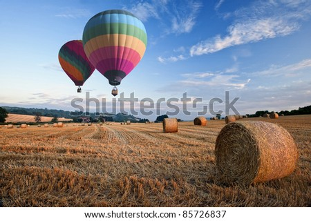 Lovely sunset golden hour landscape of hay bales in field in English countryside