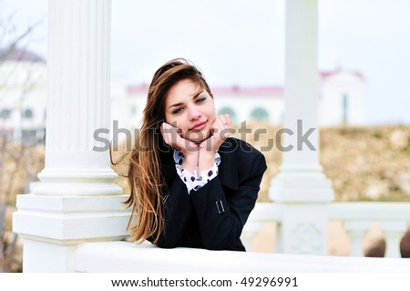 lovely sweet teen  girl standing  near columns