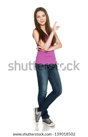 Lovely teen girl in full length standing casually and pointing to the side at blank copy space, against white background