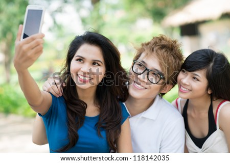 Lovely teen lady taking a picture of herself and her friends with a mobile phone