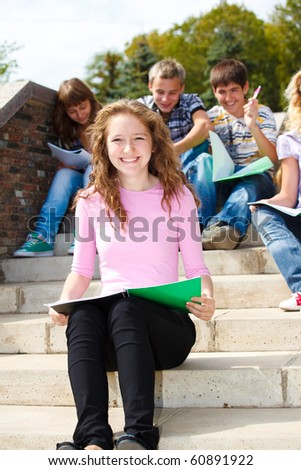 Lovely Teenage students sitting on stairway