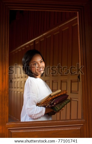 Lovely Thai girl wearing white blouse holding folded clothes looking away through window of a traditional teak wood house.  20-30 female Asian Thai model of Chinese descent