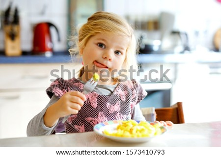 Lovely toddler girl eating healthy fried potatoes for lunch. Cute happy baby child in colorful clothes sitting in kitchen of home, daycare or nursery. Kid eats vegetables.