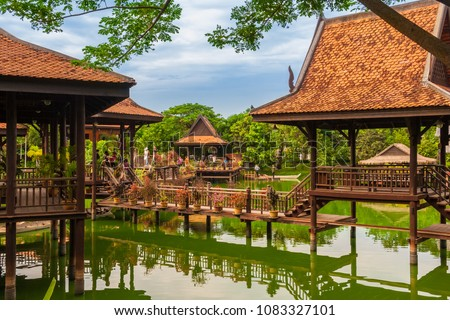 Lovely view of the floating village in the Cambodian Cultural Village in Siem Reap, Cambodia. Tourists enjoy walking on the wooden structures on stilts which are reflected by the water of the lake.