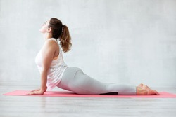 Lovely woman doing yoga exercise on a mat. Upward-facing dog pose