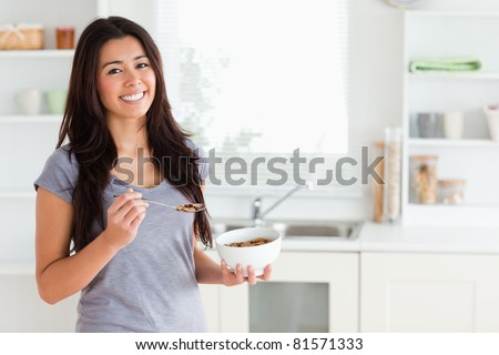 Lovely woman enjoying a bowl of cereal while standing in the kitchen