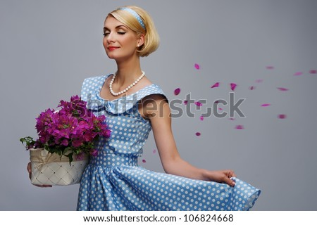 Lovely woman in a blue dress with a basket of flowers