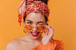 Lovely woman in African-style massive earrings and headband removes her orange glasses and winks coquettishly