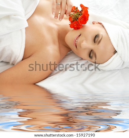 lovely woman in spa smelling red flower