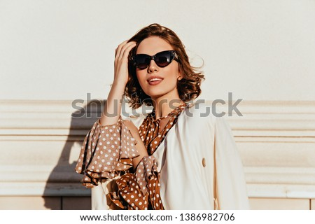 Photo of  Lovely woman in vintage outfit expressing interest. Outdoor shot of glamorous happy girl in sunglasses.