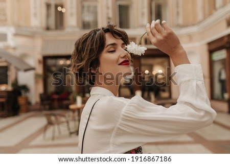Lovely woman in white shirt with long sleeve holding flower in city. Short-haired girl with red lipstick posing at street.. ストックフォト ©