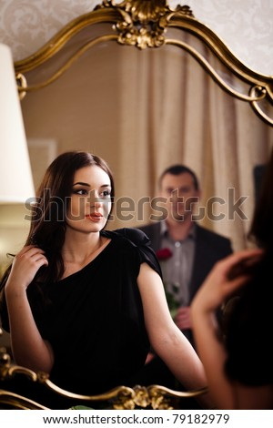 Lovely woman looking at mirror reflection. See more images from the same shoot. - stock photo
