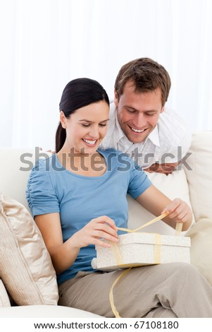 Lovely woman opening a present from her boyfriend together in the living room