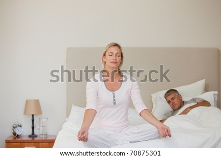 Lovely woman practicing yoga on her bed