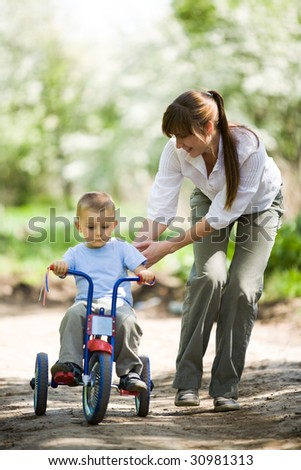 Lovely woman touching her son while he riding a bicycle in park