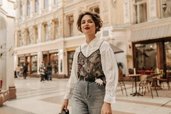 Lovely woman with wavy hair in jeans with belt and flower smiling at street. Cool lady in white blouse with lace posing in city..