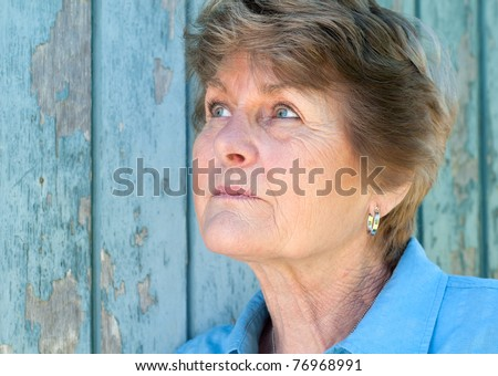 Lovely 70 year old woman looking up in thought with room or space for copy or text.