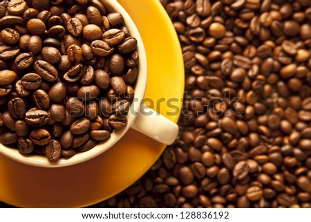 Lovely yellow cup of hot coffee and coffee beans  on a saucer with a burlap sack and roasted - stock photo