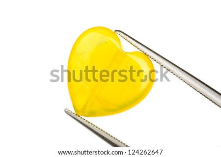 Lovely yellow opal bead in the shape of a heart. Held by tweezers.