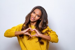 Lovely young african american woman with happy smile, shapes heart with both hands, expresses love to you, wears yellow wool sweater, says be my valentine flirts with boyfriend poses indoor copy space