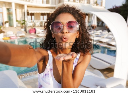 Lovely young african woman in swimsuit taking a selfie while spending good time a swimming pool resort