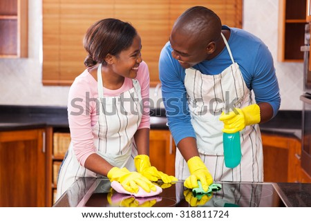 lovely young black couple cleaning together in their kitchen #318811724