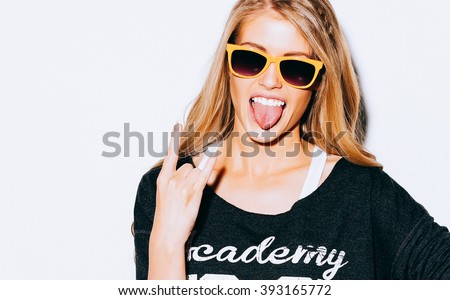 Lovely young blond woman making a call me gesture and showing tongue in suglasses, Sweatshirt and white shorts. White background. Close up. Indoor. Warm color. Hipster. #393165772